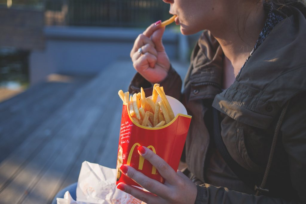 Lady eating McDonalds Fries
