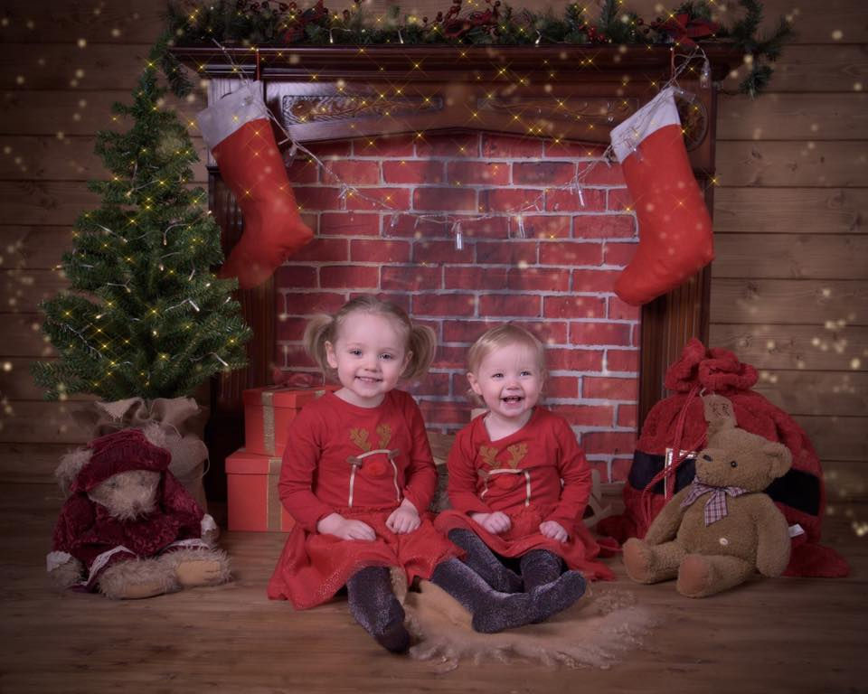 Two little girls sitting by a fireplace